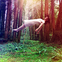 Woman hovering above the forest floor