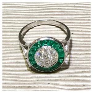Elegante anillo de diseño circular realizado en oro blanco con brillantes y esmeraldas.