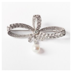 Original broche de inspiración Art Déco, diseñado en oro blanco, brillantes y detalle de perla.
