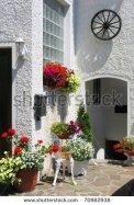 Cozy mediterranean garden with geranium flower pots,once