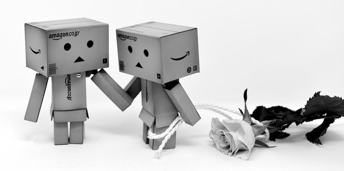 Zwei Pappmenschen halten sich an den Händen. Ein Männchen hat eine Rose in der Hand.