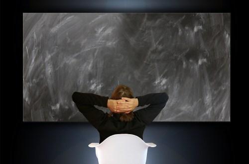 Frau sitzt mit hinter dem Kopf verschränkten Armen vor einer leeren Tafel