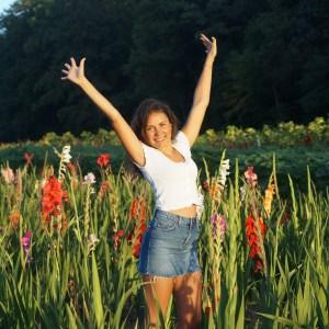 Anna steht in einer Blumenwiese und streckt die Arme in die Luft