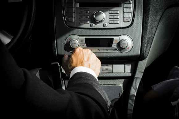 man in black suit inside limo car