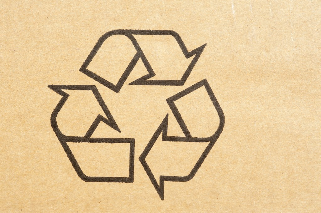 Recycle symbol stamped on brown cardboard