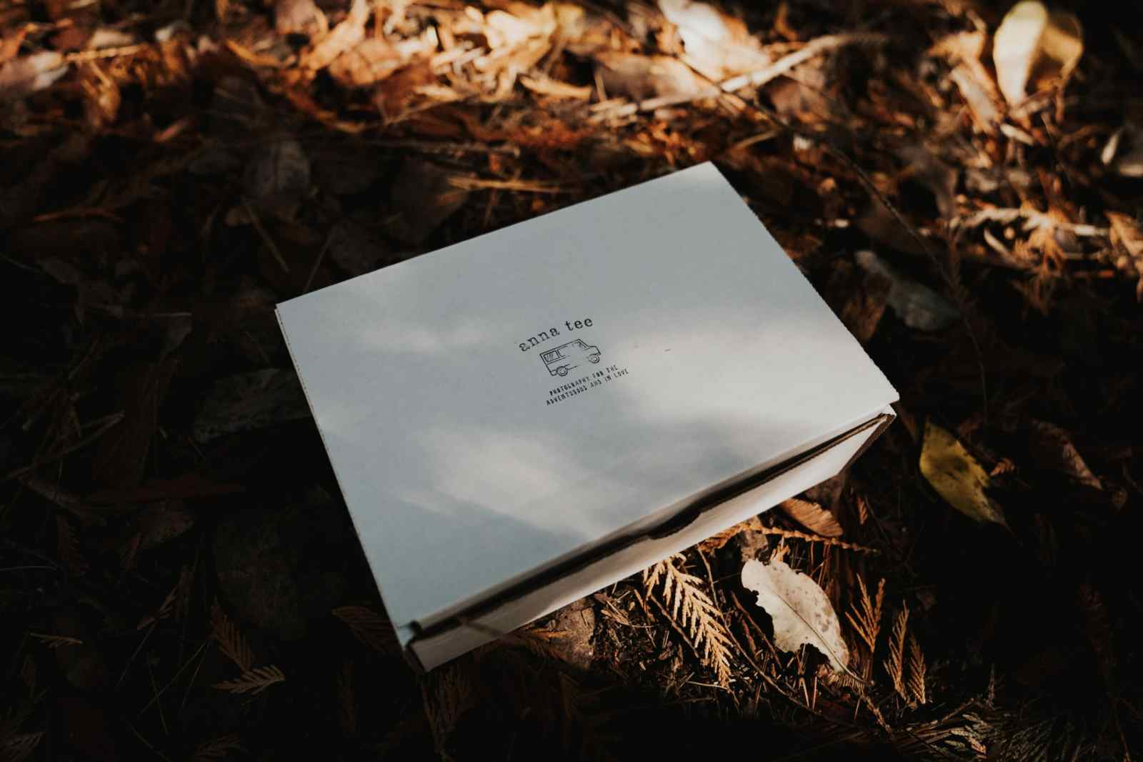 A white wedding photography client gift box is lying on the ground, on top of some brown leaves.