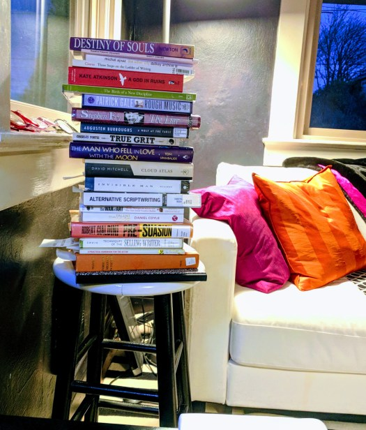 A tall stack of books on a stool in my living room