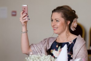 Wedding guest taking a photo with her iPhone