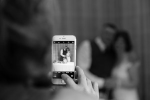 Guest photographing Bride and Groom with a mobile phone