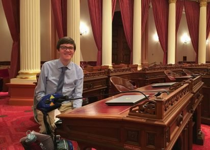 Journalism student Hawken Miller is standing inside the capitol building main hall in Sacramento.