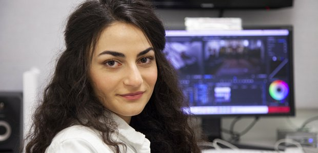 USC Annenberg Masters student, Shushan Minasian, photographed sitting near a computer, and looking back into the camera.
