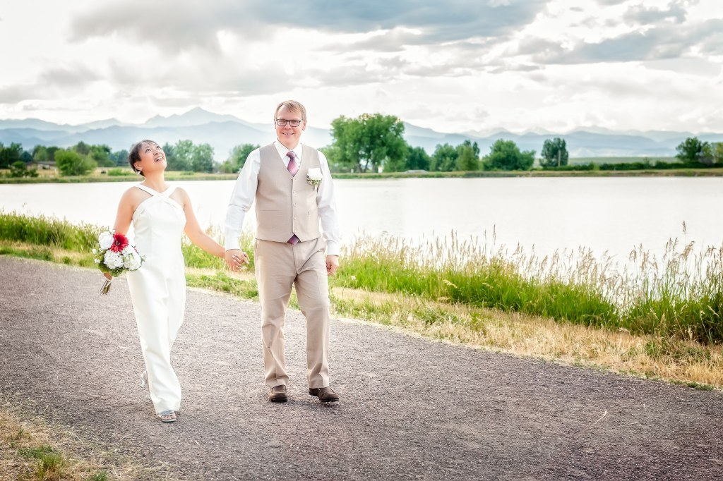 A newly married couple takes a short break between the ceremony and reception to enjoy a beautiful walk along a lake.