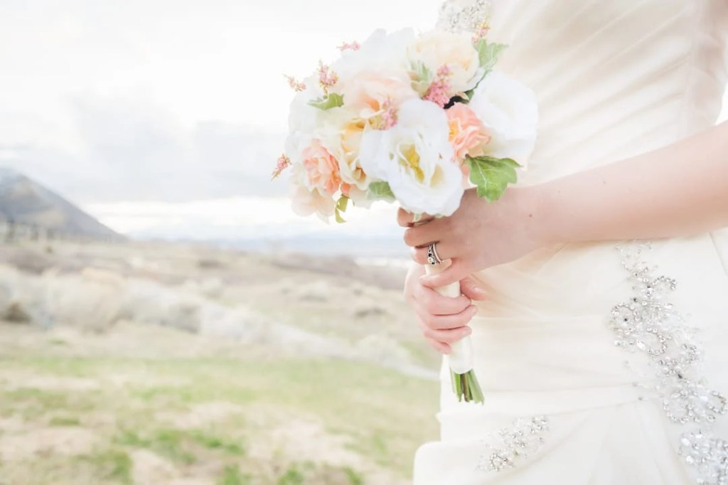 A woman holds a wedding bouquet.