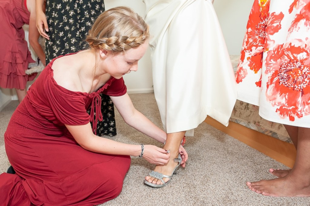 A young woman helps the bride get ready by helping with her shoes.