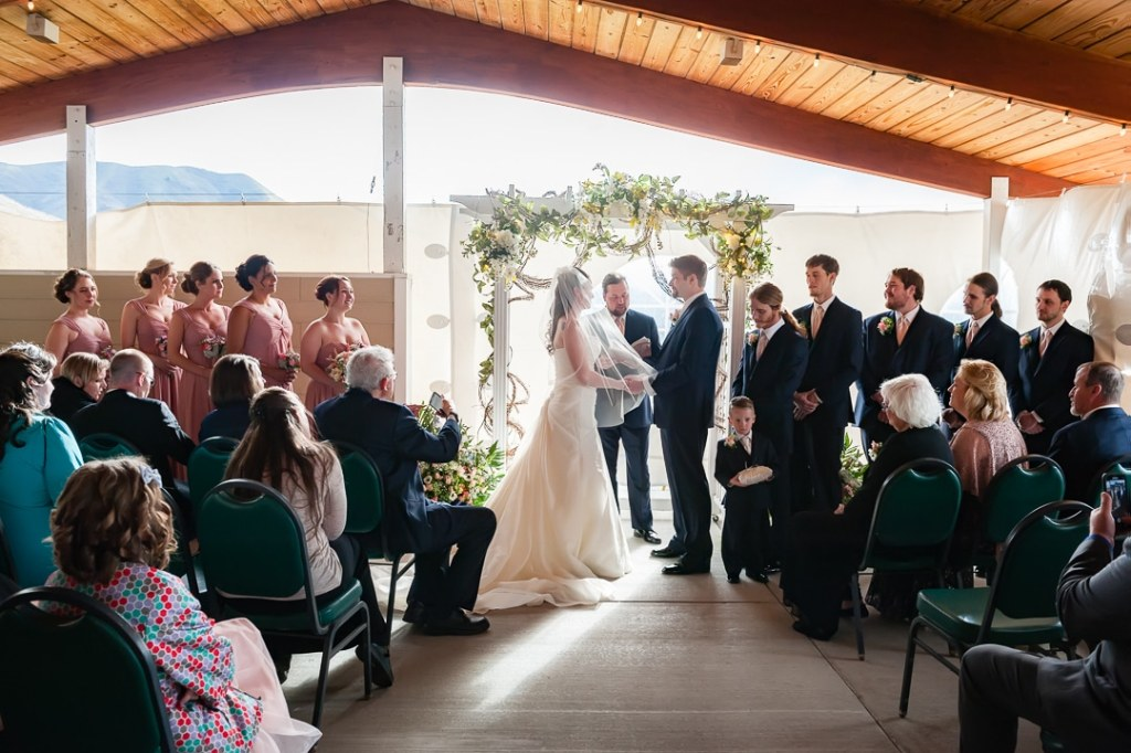 A wedding couple state their vows in the company of friends and family.