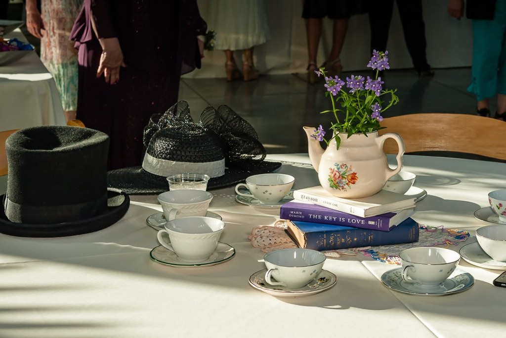Teapots, books and hats add style to the table of this tea-party themed wedding.
