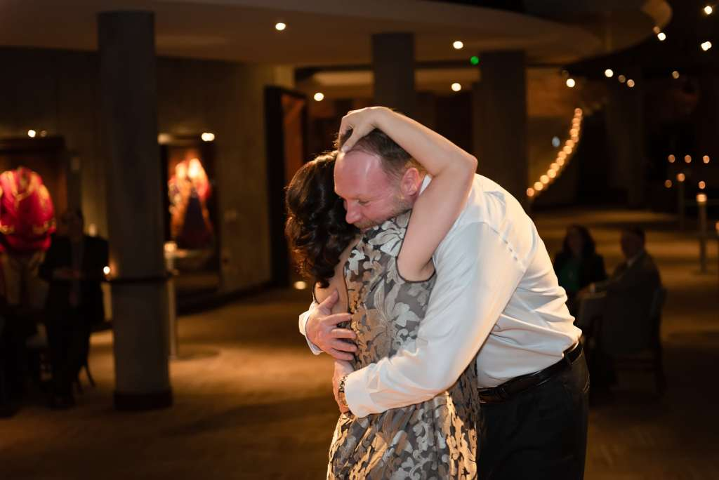A bride and groom share an emotional moment on the dance floor.