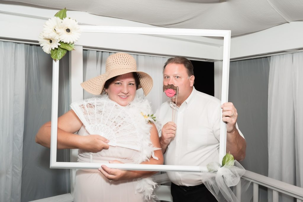 The mother and father of the bride pose using the props in a DIY photo booth.
