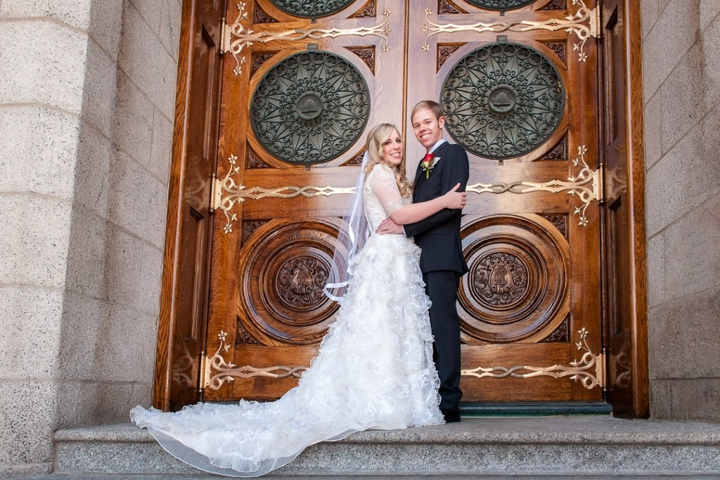 A newly married couple poses on the steps of the LDS temple after their church wedding.