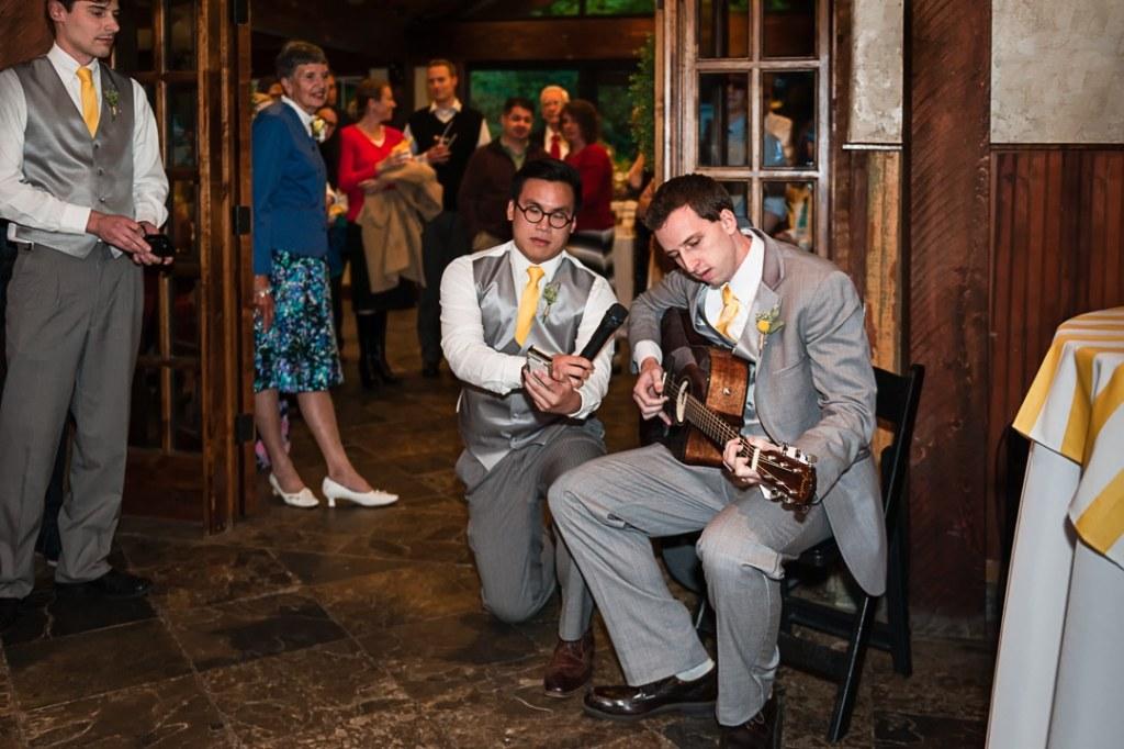 A groom plays a guitar and serenades his bride.