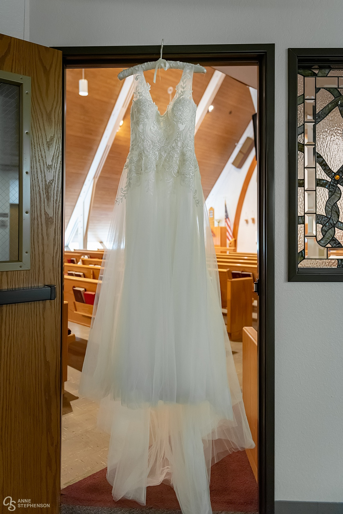 The bride's dress framed by the doorway into the church.