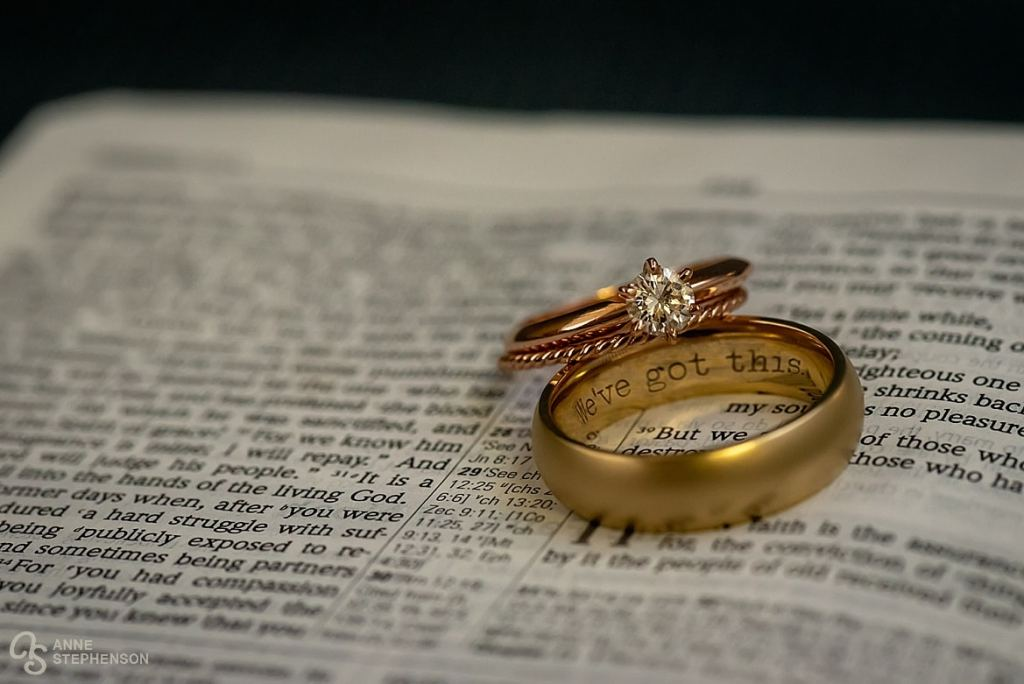 The bride and groom's rings rest on a favorite bible passage.