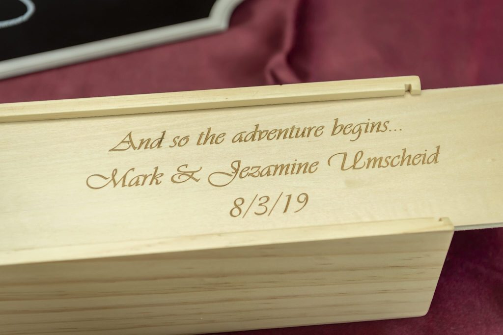 The lid of a Jenga game etched with the names and wedding date of the bride and groom.