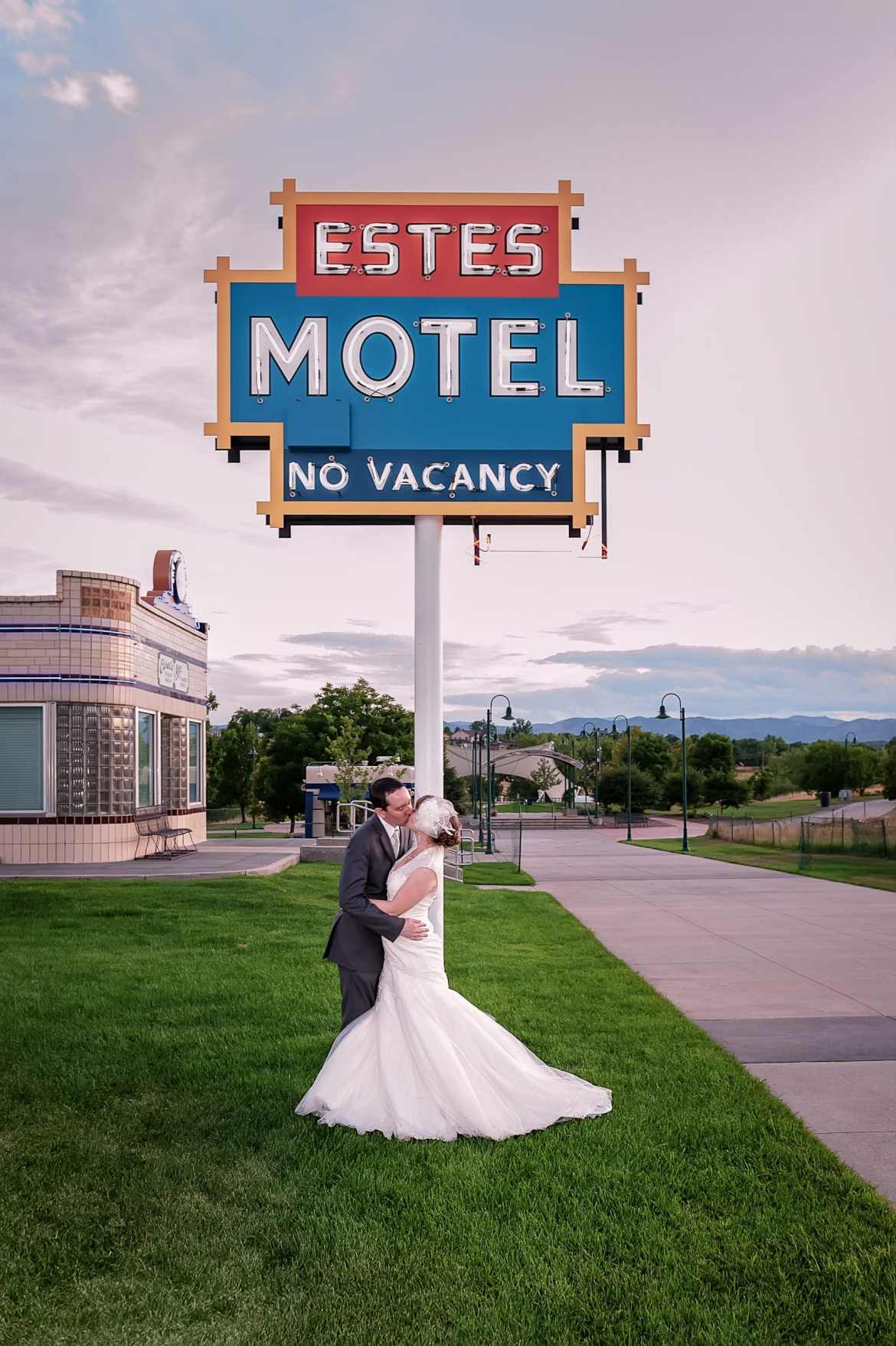 The wedding couple kisses under the historic Estes Motel Sign at the Lakewood Heritage Center that states: No Vacancy.