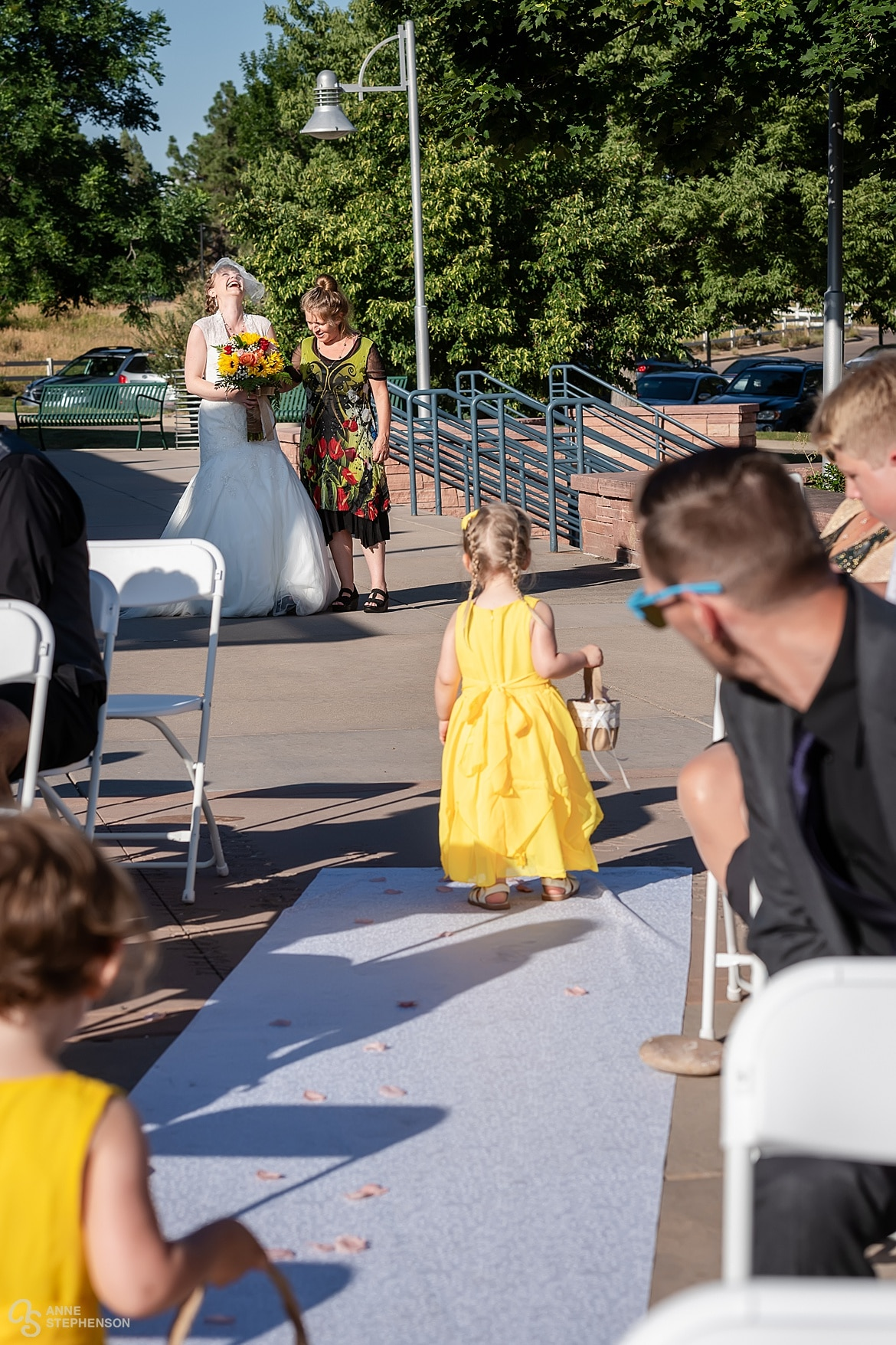 The bride laughs when seeing the flower girls back down the aisle dropping flower petals.