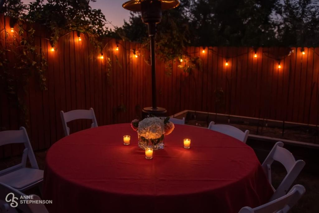 Votive candles and twinkle lights create a beautiful ambiance for the back yard party.