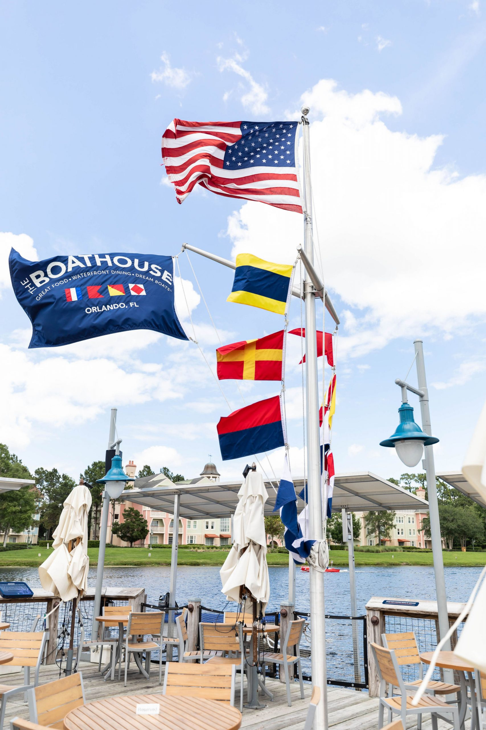 Walt Disney World's Boathouse Restaurant and Nautical Flags Striped Cabanas Along the Shore Photographed by Luxury Travel Writer Annie Fairfax