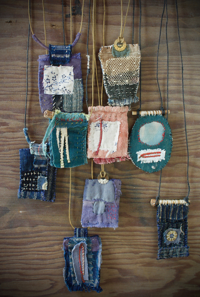 colorful fabric pendants on a worn piece of wood