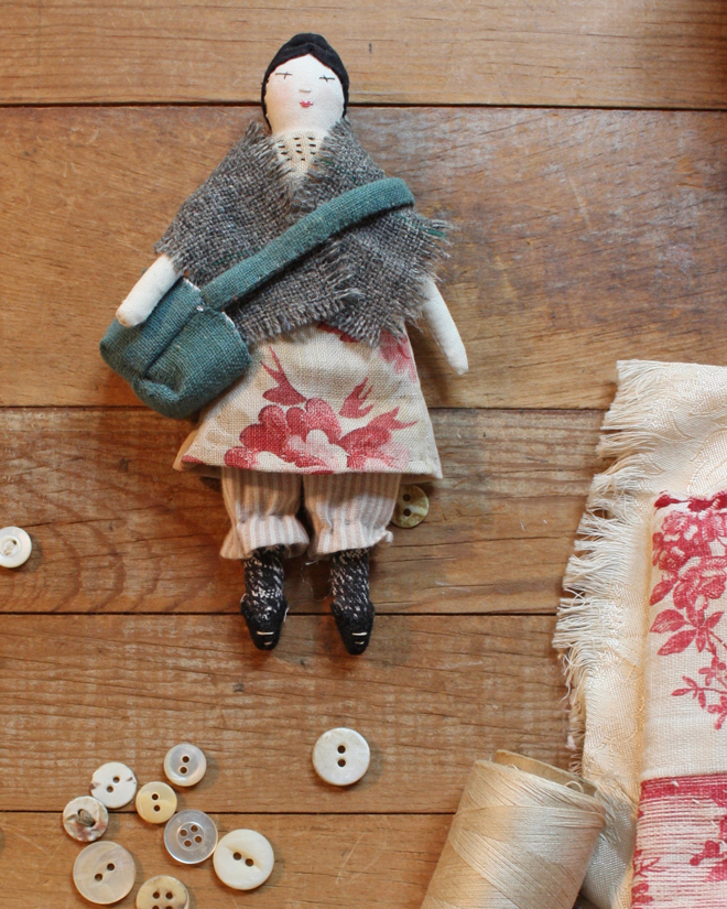 tiny rag doll with a shawl and satchel