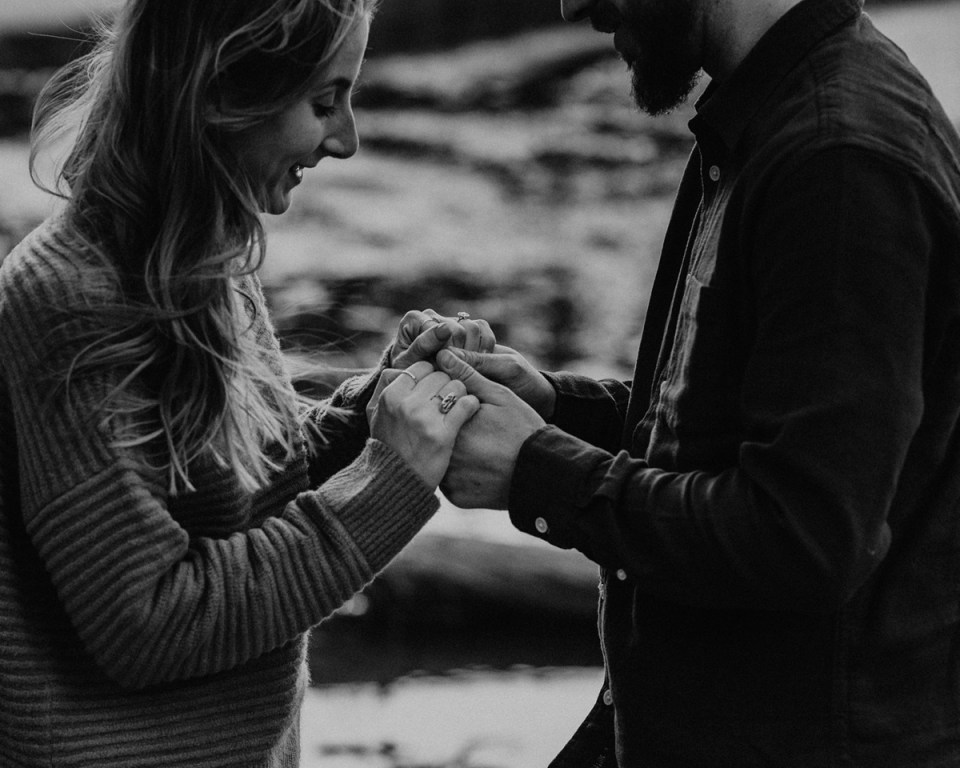 Couple admiring engagement ring after proposal during their Rocky Mountain National Park engagement photos.
