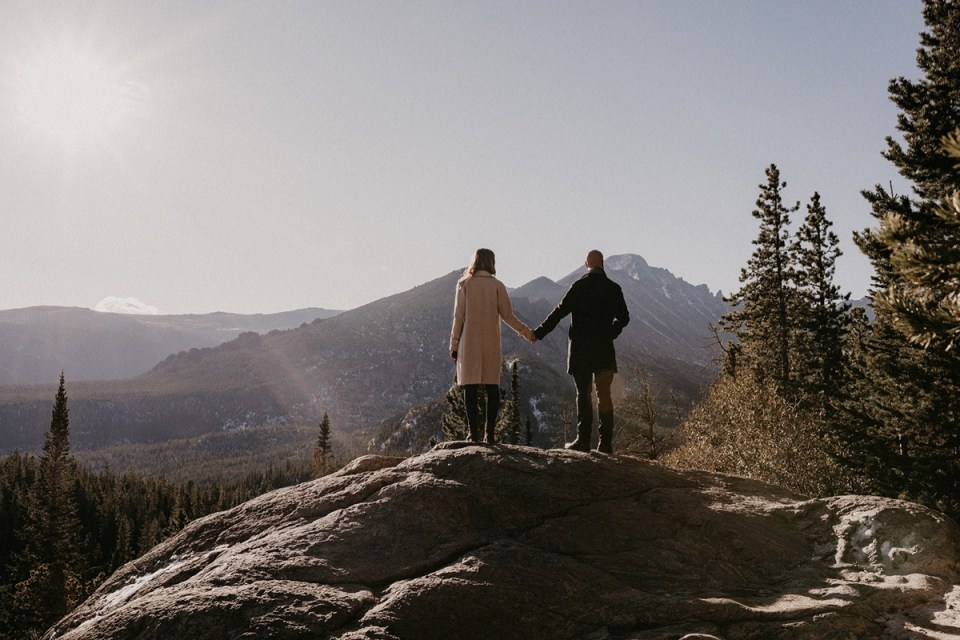 Couple holding hands on ledge of mountain during their Rocky Mountain National Park engagement photos.
