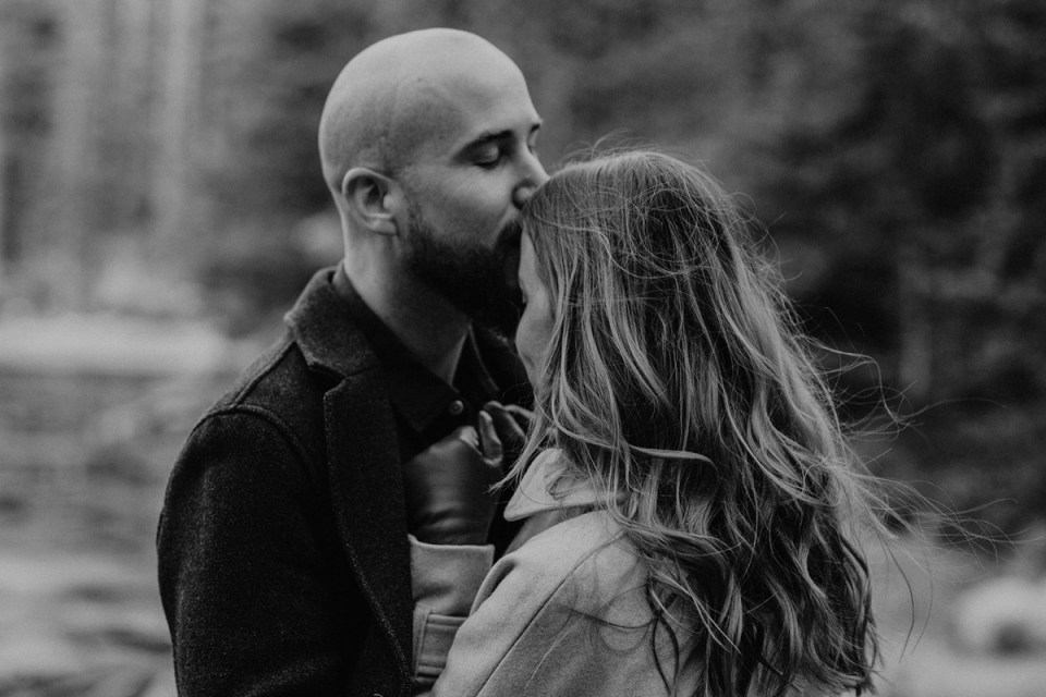Man kissing his fiance during their Rocky Mountain National Park engagement photos.
