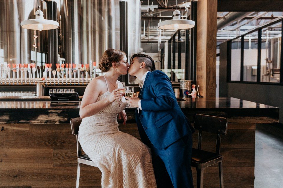 Couple celebrating by popping champagne after getting married.