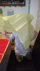 toddler covered in tissue paper