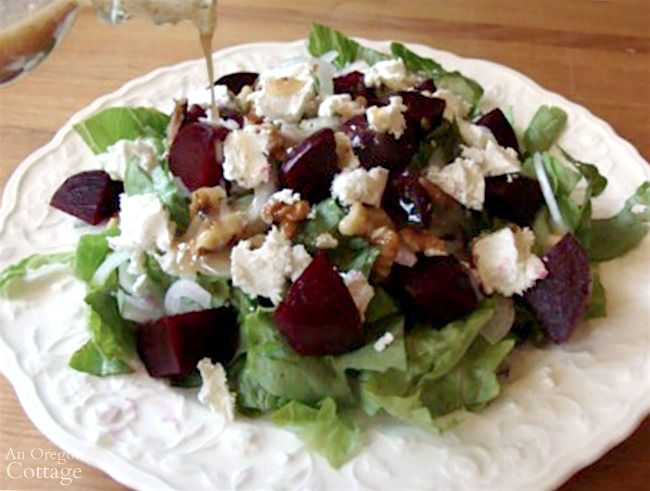 Roasted beet salad with goat cheese and walnuts-pouring dressing