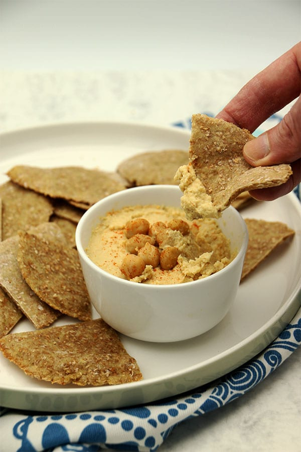 hummus with flatbread triangles on plate being dipped