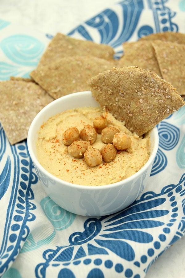 hummus and flatbread on blue cloth