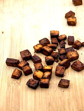 Smokey tofu bacon cubes on wooden board