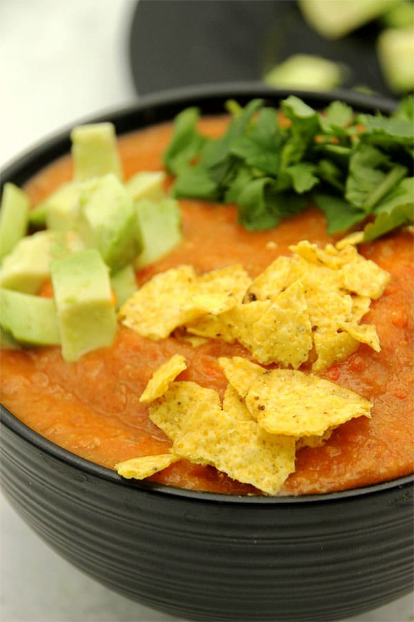 Easy vegan tortilla soup in black bowl with tortilla chips, avocado and coriander on top and plate behind with garnishes