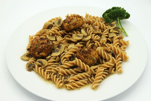 Baked veggie balls on pasta with mushroom gravy