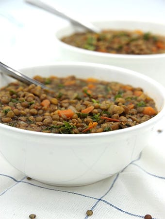 Vegan French lentil soup in 2 white bowls with spoons