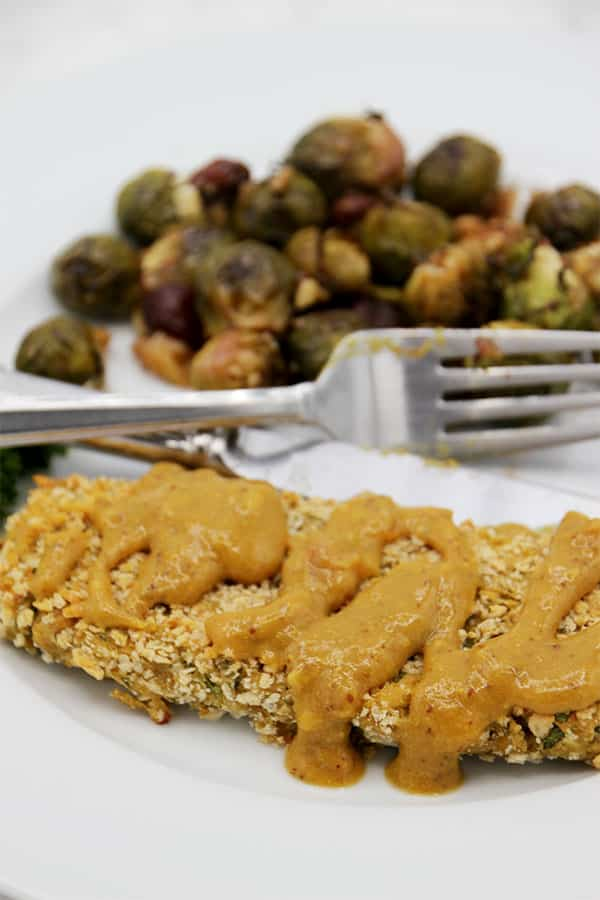chickpea cutlet with mustard sauce on plate with fork. Brussels sprouts and grapes in background.