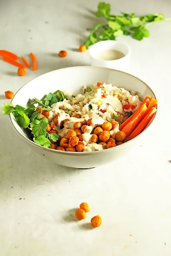 buffalo chickpea bowl with dressing in back and chickpeas on board.