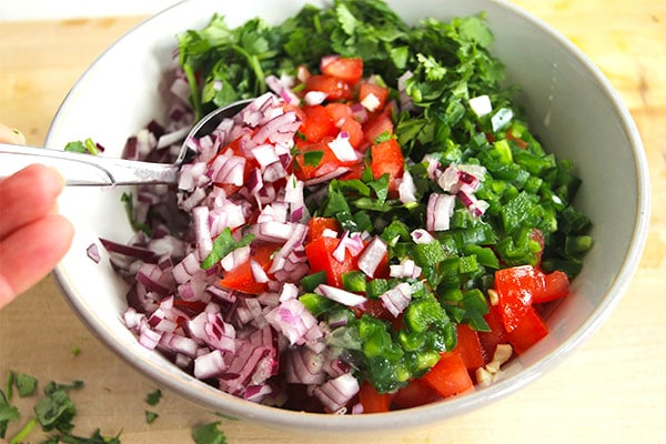 DIY pico de gallo in a bowl being mixed with a spoon