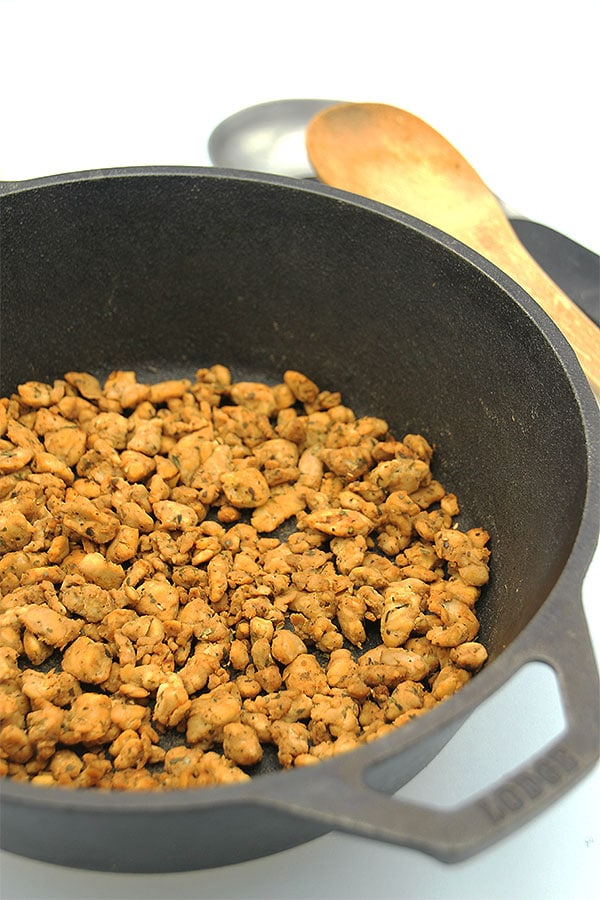 Perfect tempeh crumbles in black pan with spoon in background
