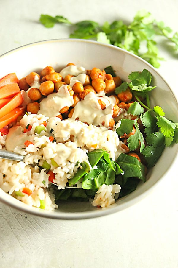Buffalo chickpea bowl with dressing and spoon on grey board